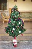 Άγιος Βασίλης και ένα χριστουγεννιάτικο δέντρο σε ένα patio Στοκ εικόνα με δικαίωμα ελεύθερης χρήσης