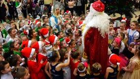 Άγιος Βασίλης και κορίτσι χιονιού που περιβάλλονται από τα παιδιά των αθλητών απόθεμα βίντεο