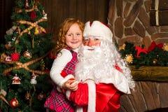 Άγιος Βασίλης κρατά σε ετοιμότητα το ευτυχές μικρό κορίτσι Στοκ εικόνα με δικαίωμα ελεύθερης χρήσης