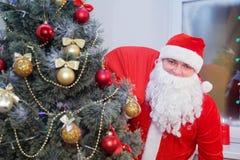 Άγιος Βασίλης με μια τσάντα κοντά στο χριστουγεννιάτικο δέντρο Στοκ Φωτογραφία