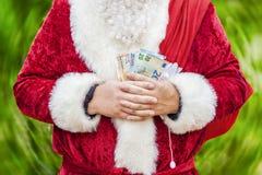 Άγιος Βασίλης με τα ευρο- τραπεζογραμμάτια και τσάντα δώρων σε πράσινο Στοκ Εικόνες