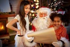 Άγιος Βασίλης με τα μικρά κορίτσια που διαβάζουν τη λίστα επιθυμητών στόχων Στοκ φωτογραφία με δικαίωμα ελεύθερης χρήσης