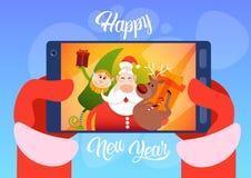 Άγιος Βασίλης με τον τάρανδο Elfs που κάνει τη φωτογραφία Selfie, νέα ευχετήρια κάρτα διακοπών Χριστουγέννων έτους ελεύθερη απεικόνιση δικαιώματος