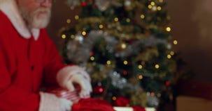 Άγιος Βασίλης με το δάχτυλο στα χείλια που βάζει τα κιβώτια δώρων στην τσάντα Χριστουγέννων απόθεμα βίντεο