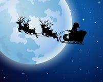 Άγιος Βασίλης οδηγά τη σκιαγραφία ελκήθρων ταράνδων σε ένα κλίμα πανσελήνων Στοκ Εικόνες