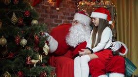 Άγιος Βασίλης παρουσιάζει σε ένα μικρό κορίτσι μαγικά παιχνίδια στο χριστουγεννιάτικο δέντρο απόθεμα βίντεο