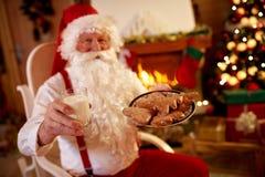 Άγιος Βασίλης που απολαμβάνει στο παραδοσιακό πρόχειρο φαγητό Χριστουγέννων στοκ φωτογραφία με δικαίωμα ελεύθερης χρήσης