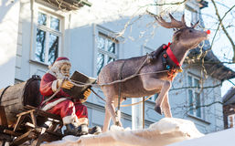 Άγιος Βασίλης που διαβάζει ένα βιβλίο στο έλκηθρο με έναν τάρανδο Στοκ φωτογραφία με δικαίωμα ελεύθερης χρήσης