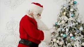 Άγιος Βασίλης που διακοσμεί το χριστουγεννιάτικο δέντρο με τα μπιχλιμπίδια απόθεμα βίντεο