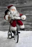 Άγιος Βασίλης που κάνει τα Χριστούγεννα ψωνίζοντας με το ποδήλατό του αστεία ιδέα στοκ εικόνα