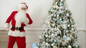 Άγιος Βασίλης που κάνει τον αστείο χορό ρομπότ δίπλα στο χριστουγεννιάτικο δέντρο απόθεμα βίντεο