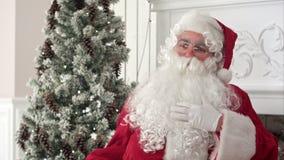 Άγιος Βασίλης που κτυπά τη λευκιά σαν το χιόνι γενειάδα του που σκέφτεται για οι επιθυμίες φιλμ μικρού μήκους