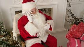 Άγιος Βασίλης που μιλά πέρα από το τηλέφωνο που επιθυμεί τη Χαρούμενα Χριστούγεννα απόθεμα βίντεο