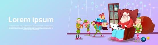 Άγιος Βασίλης που χρησιμοποιεί την πράσινη ομάδα αρωγών νεραιδών lap-top με το παρόν έμβλημα Χαρούμενα Χριστούγεννας καλής χρονιά ελεύθερη απεικόνιση δικαιώματος