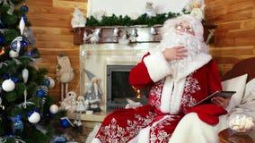 Άγιος Βασίλης που χρησιμοποιεί τη συσκευή, συνεδρίαση Αγίου Nicolas στην καρέκλα με τη ηλεκτρονική συσκευή, νέες ιδέες φιλμ μικρού μήκους