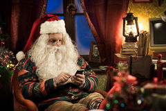 Άγιος Βασίλης που χρησιμοποιεί το smartphone στοκ εικόνα
