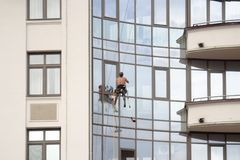 Άγιος Πετρούπολη, Ρωσία - 8 Ιουλίου 2017: Ο ορειβάτης πλένει τα παράθυρα σε ένα νέο κατοικημένο κτήριο στο νησί Krestovsky στοκ φωτογραφία