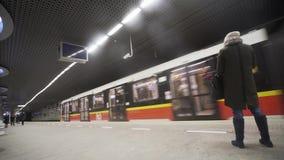 Άγνωστα νέα γυναίκα και τραίνο που φθάνουν στο σταθμό μετρό Rondo ONZ Βαρσοβία, Πολωνία Στοκ Φωτογραφία