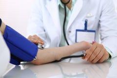 Άγνωστη γυναίκα γιατρών που ελέγχει τη πίεση του αίματος του θηλυκού ασθενή, κινηματογράφηση σε πρώτο πλάνο Καρδιολογία στην ιατρ στοκ φωτογραφία με δικαίωμα ελεύθερης χρήσης