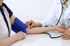 Άγνωστη γυναίκα γιατρών που ελέγχει τη πίεση του αίματος του θηλυκού ασθενή, κινηματογράφηση σε πρώτο πλάνο Καρδιολογία στην ιατρ στοκ εικόνες