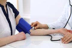 Άγνωστη γυναίκα γιατρών που ελέγχει τη πίεση του αίματος του θηλυκού ασθενή, κινηματογράφηση σε πρώτο πλάνο Καρδιολογία στην ιατρ στοκ εικόνα με δικαίωμα ελεύθερης χρήσης