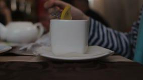 Άγνωστη συνεδρίαση γυναικών στον καφέ, που βάζει το λεμόνι στο άσπρο φλυτζάνι απόθεμα βίντεο