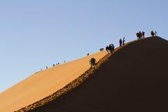 Άγνωστοι άνθρωποι που αναρριχούνται επάνω στον αμμόλοφο για να δει την ανατολή στη Ναμίμπια Στοκ Εικόνα