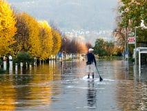 Άγνωστοι άνθρωποι που κάνουν σερφ στον πλημμυρισμένο δρόμο Στοκ Εικόνα