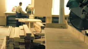 Άγνωστοι ξυλουργοί και ένα τορνευτικό πριόνι σε ένα εργαστήριο ξυλουργικής Στοκ Φωτογραφία