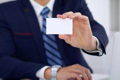 Άγνωστος επιχειρηματίας ή δικηγόρος που δίνει μια επαγγελματική κάρτα καθμένος στον πίνακα, κινηματογράφηση σε πρώτο πλάνο Αυτός  Στοκ Φωτογραφία