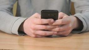 Άγνωστος σπουδαστής που κρατά το μαύρο smartphone απόθεμα βίντεο