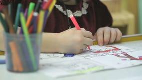 Άγνωστο λίγο παιδί χρωματίζει τις εικόνες με την πίλημα-άκρη απόθεμα βίντεο