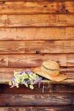 Άγρια λουλούδια με το καπέλο αχύρου στους παλαιούς πίνακες Στοκ Εικόνες