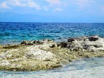 Άγρια παραλία, δύσκολη ακτή με το aquamarine, μπλε, τυρκουάζ wat Στοκ Φωτογραφία