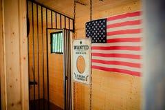 Άγρια πόρτα δυτικών φυλακών και επιθυμητό σημάδι με τη αμερικανική σημαία στο BA Στοκ φωτογραφία με δικαίωμα ελεύθερης χρήσης