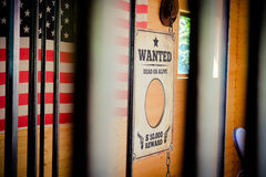 Άγρια δυτική φυλακή και επιθυμητό σημάδι με τη αμερικανική σημαία στο backgro Στοκ Εικόνα