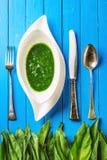 Άγρια φύλλα σκόρδου με τη σούπα σκόρδου στο άσπρο πιάτο και τα μαχαιροπήρουνα στο μπλε ξύλινο υπόβαθρο, υγιής τρόπος ζωής, εποχια Στοκ Εικόνες