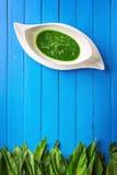 Άγρια φύλλα σκόρδου με τη σούπα σκόρδου στο άσπρο πιάτο στο μπλε ξύλινο υπόβαθρο, υγιής τρόπος ζωής, εποχιακό χορτάρι άνοιξη για  Στοκ φωτογραφία με δικαίωμα ελεύθερης χρήσης