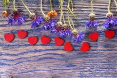 Άγριες λουλούδια και καρδιές στο ξύλο στοκ φωτογραφία με δικαίωμα ελεύθερης χρήσης