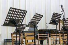 Άδειες θέσεις και μερικά όργανα στο μέγαρο μουσικής που αναμένει την ορχήστρα για να έρθει στο στάδιο μαύρη στάση μουσικής στη σκ στοκ φωτογραφίες