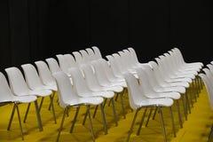 Άδειες θέσεις σειρών ακροατηρίων κίτρινο πάτωμα καρεκλών δωματίων στο άσπρο Στοκ φωτογραφία με δικαίωμα ελεύθερης χρήσης