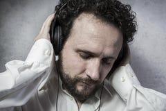 Άκουσμα και απόλαυση της μουσικής με τα ακουστικά, άτομο στο άσπρο πουκάμισο Στοκ Εικόνες