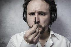 Άκουσμα και απόλαυση της μουσικής με τα ακουστικά, άτομο στο άσπρο πουκάμισο Στοκ Εικόνα