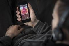 Άκουσμα τη μουσική με Spotify app που χρησιμοποιεί το iPhone 5s Στοκ Φωτογραφίες