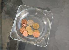 Άκρες που αφήνονται ashtray σε έναν πίνακα γυαλιού στοκ φωτογραφίες