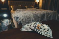 άκρη δωματίων κρεβάτι και χρήματα για να συμβολίσει το κόστος του φύλου Πληρωμένη αγάπη η πόρνη Πληρωμή για τις υπηρεσίες των πορ στοκ εικόνα με δικαίωμα ελεύθερης χρήσης