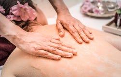 Άλας τριψίματος χεριών στην πλάτη γυναικών για Skincare Στοκ Φωτογραφία