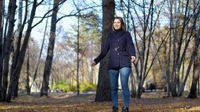 Άλματα γυναικών ευτυχώς μεταξύ των δέντρων και των φύλλων φθινοπώρου σε αργή κίνηση 4k 60fps Κορίτσι σε ένα παλτό που περπατά στο φιλμ μικρού μήκους