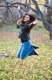 Άλματα κοριτσιών στο πάρκο το φθινόπωρο στοκ εικόνες