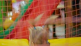 Άλματα μικρών κοριτσιών σε ένα φωτεινό πολύχρωμο εσωτερικό τραμπολίνο απόθεμα βίντεο